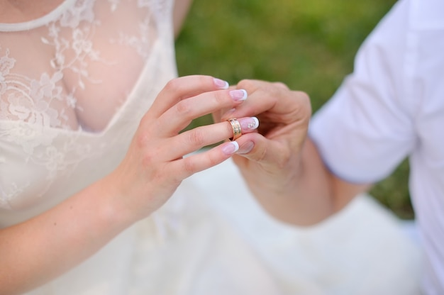 Jovem noivo veste a noiva do anel. isolado no fundo branco Foto Premium