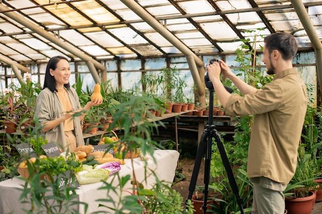 Jovem nutricionista asiática segurando uma abóbora e fazendo um vídeo sobre comida em estufa Foto Premium
