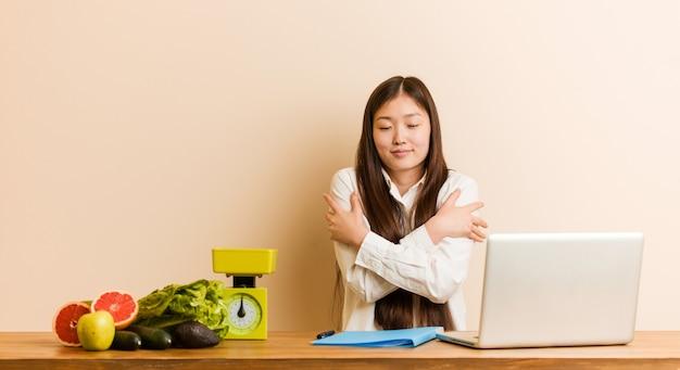Jovem nutricionista chinesa que trabalha com seu laptop se abraça, sorrindo despreocupada e feliz. Foto Premium