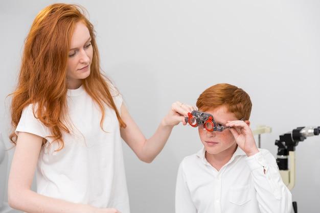 Jovem oculista feminina usando quadro experimental de optometrista para menino bonito para verificar seus olhos Foto gratuita