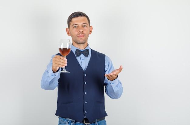 Jovem oferecendo bebida alcoólica em terno, jeans Foto gratuita