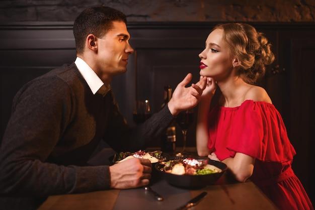 Jovem olha para os olhos de uma mulher atraente e elegante em um vestido vermelho no restaurante. relacionamento de lindo casal apaixonado, noite romântica Foto Premium