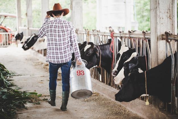 Jovem ou agricultor com balde caminhando ao longo do estábulo e vacas na fazenda de gado leiteiro Foto gratuita