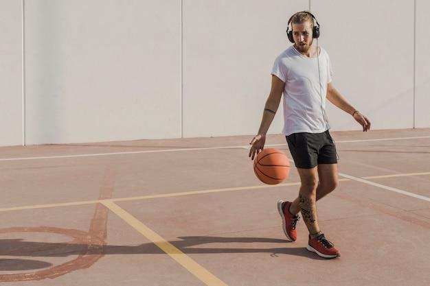 Jovem ouvindo música enquanto estiver jogando basquete no tribunal Foto gratuita