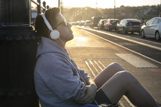 Jovem ouvindo música na rua Foto Premium
