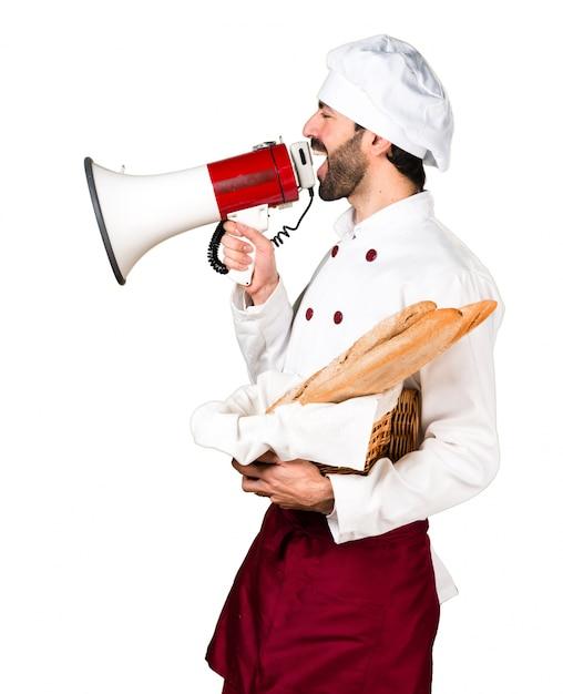 Jovem padeiro segurando um pouco de pão e gritando por megafone Foto gratuita