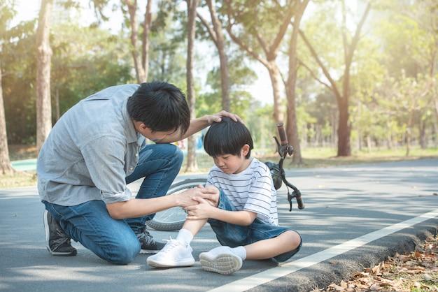 Jovem pai asiático do pai acalma o filho que caiu da bicicleta e ele se machuca no joelho e na perna enquanto tem lazer de fim de semana em parque público, o acidente pode acontecer em todos os lugares e sempre. Foto Premium
