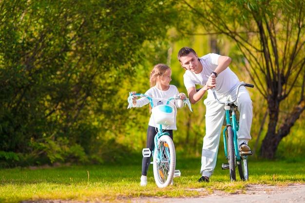 Jovem pai e filha andando de bicicleta no dia quente de verão Foto Premium