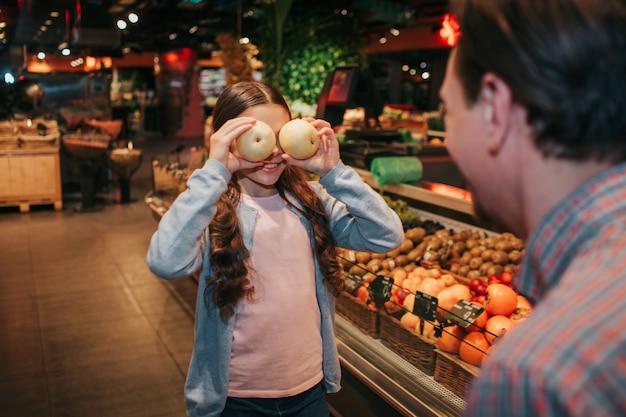 Jovem pai e filha na mercearia. ela cobre os olhos com maçãs e sorri. pai olhe para ela. compras divertidas e engraçadas. Foto Premium