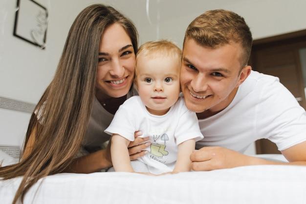 Jovem pai e mãe estão felizes nos braços de seu filho Foto gratuita