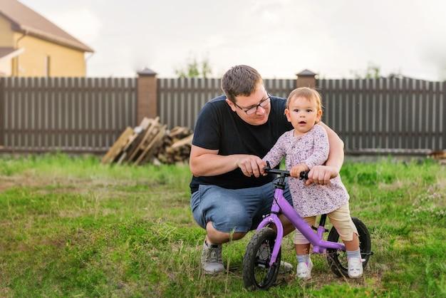 Jovem, pai, gastar tempo, com, cute, pequeno, um, anos velho, toddler, criança menina, e, equilíbrio, bicicleta Foto Premium