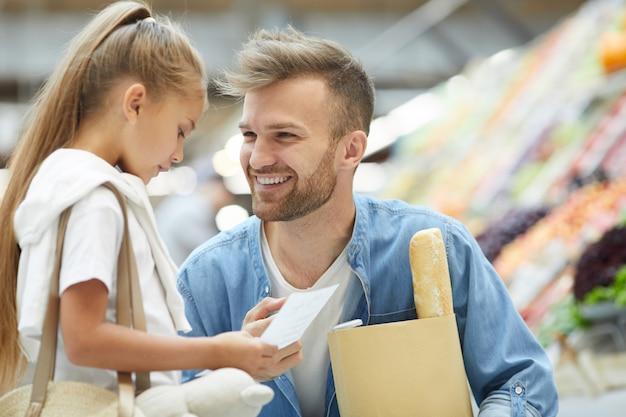 Jovem pai no supermercado Foto Premium
