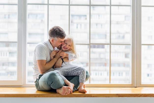 Jovem pai rindo com filha enquanto está sentado na frente da janela. pai feliz abraça linda garota enquanto se diverte juntos Foto Premium