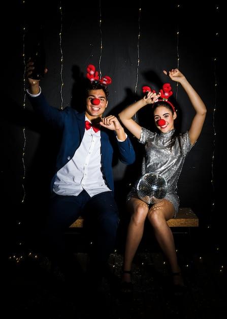 Jovem, par, com, veado, chifres, headbands, e, engraçado, narizes, com, bola discoteca Foto gratuita
