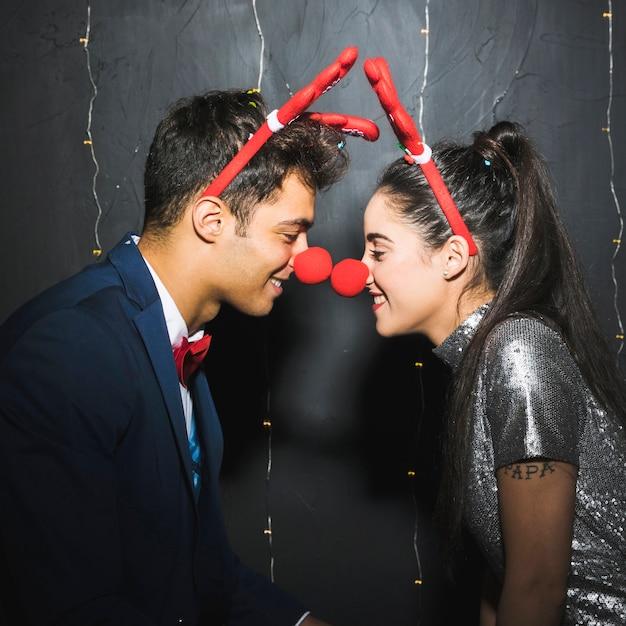 Jovem, par feliz, com, veado vermelho, antlers headbands, e, engraçado, narizes Foto gratuita