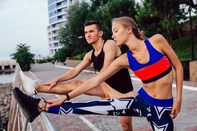 Jovem, par saudável, fazendo, esportes, exercícios, para, pernas, desgastar, sportswear, malhação, ao ar livre Foto gratuita