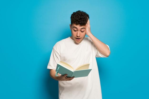 Jovem parede azul surpreendido enquanto desfruta de ler um livro Foto Premium