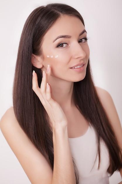 Jovem passa hidratante no rosto Foto Premium