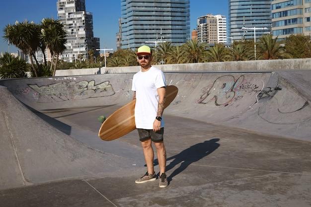 Jovem patinador tatuado e atraente com boné de caminhoneiro em t-shitrt branco sem rótulo com seu longboard de madeira na mão no centro do skatepark, paisagem urbana atrás Foto gratuita