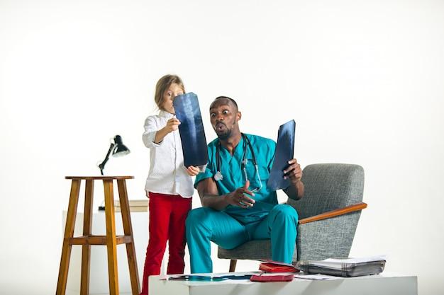 Jovem pediatra masculino africano, explicando o raio-x para criança Foto gratuita