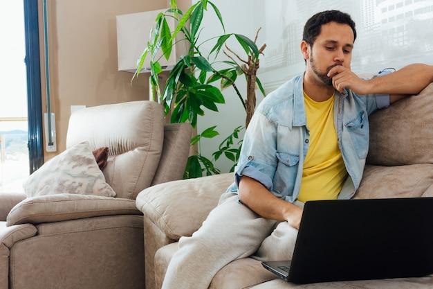 Jovem pensando em algo em casa em seu sofá e olhando para um laptop Foto gratuita