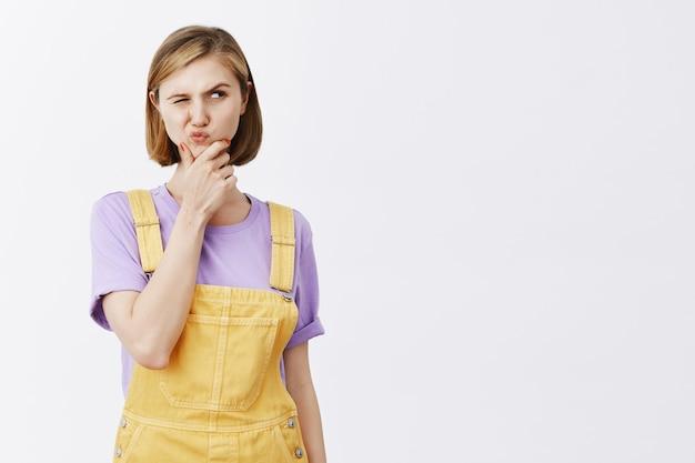 Jovem pensativa e desconfiada franzindo a testa e parecendo curiosa, pensando, tomando decisões Foto gratuita