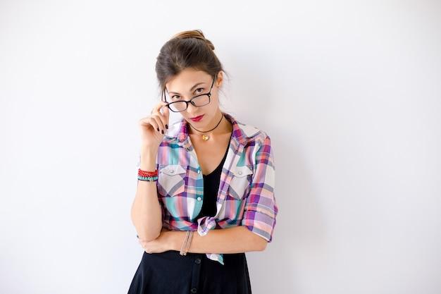 Jovem pensativa usando óculos Foto gratuita