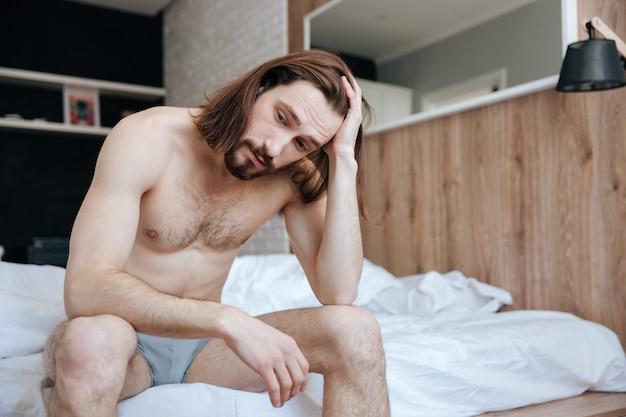 Jovem pensativo cansado sentado e pensando na cama Foto gratuita
