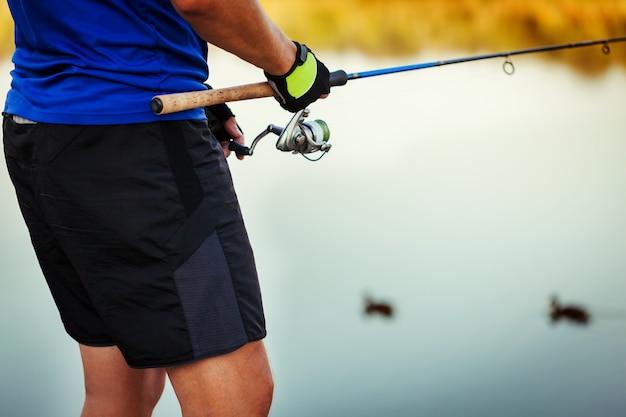 Jovem pesca no rio ao pôr do sol. closeup de pescador segurando a haste. equipamento de pesca. fiação Foto Premium