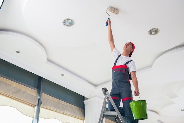 Jovem pintor pintando o teto no conceito de construção Foto Premium