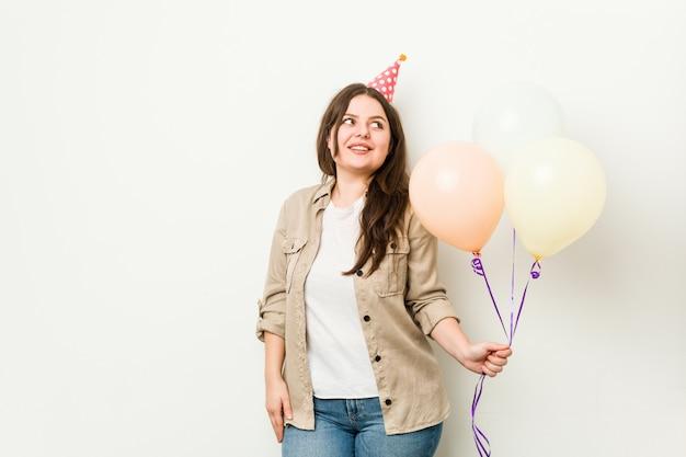 Jovem plus size mulher curvilínea comemorando um aniversário parece de lado sorrindo, alegre e agradável Foto Premium