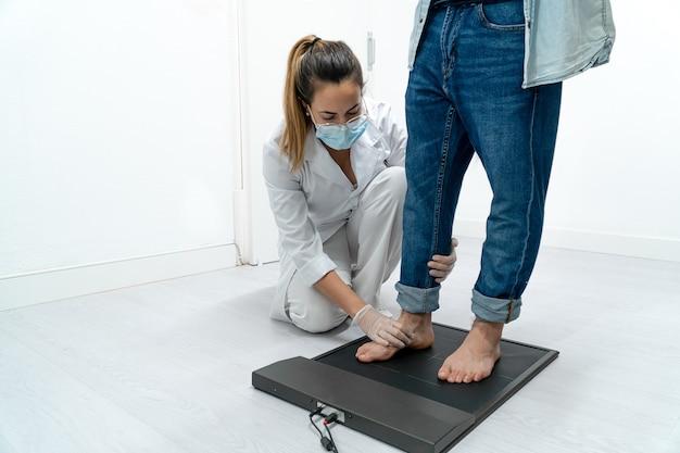 Jovem podólogo examinando os pés de um paciente em uma plataforma de pressão Foto Premium
