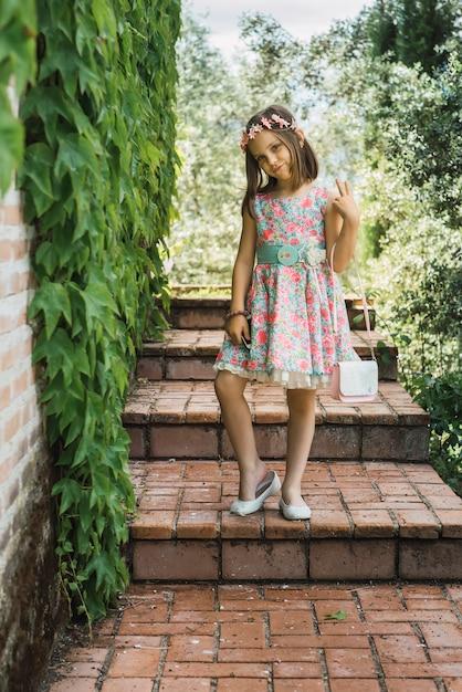 Jovem posando na escada do jardim Foto Premium