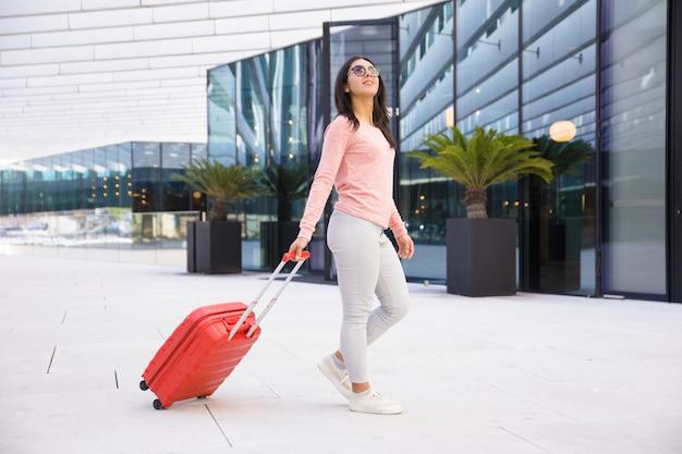 Jovem positiva em óculos de sol saindo do hall do aeroporto Foto gratuita