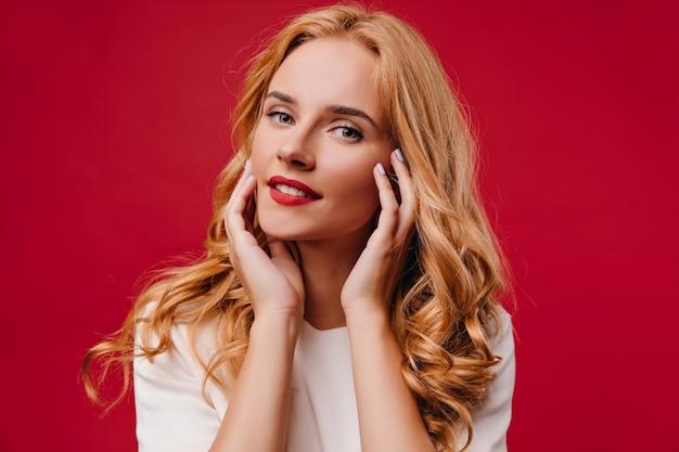 Jovem positiva posando com um sorriso encantador. garota loira alegre isolada na parede vermelha. Foto gratuita
