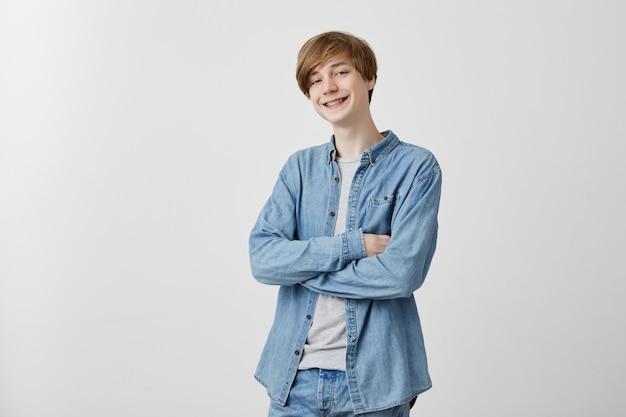 Jovem positivo na camisa jeans com cabelos loiros e olhos azuis, tímido, sorrindo nervosamente em postura fechada, mantendo os braços cruzados enquanto conversava com a garota, ele gosta Foto gratuita