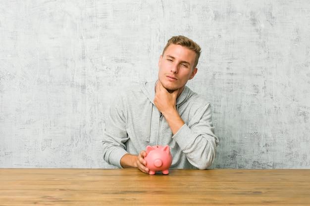 Jovem, poupar dinheiro com um cofrinho sofre dor na garganta devido a um vírus ou infecção. Foto Premium