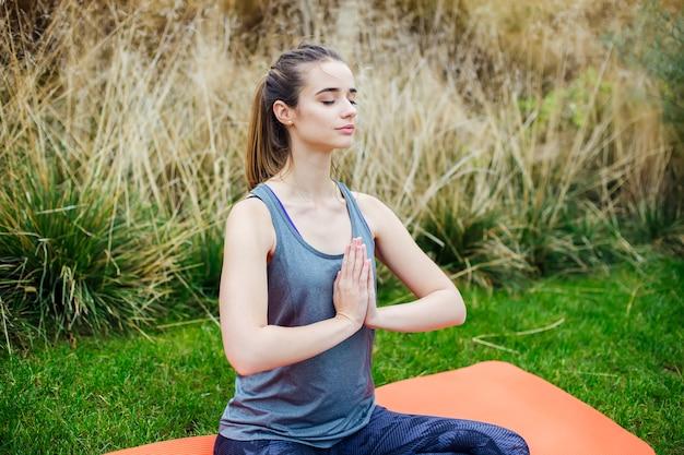 Jovem pratica ioga e medita na posição de lótus no parque Foto Premium