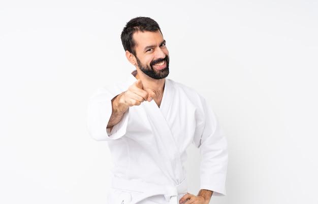 Jovem praticando karatê sobre pontos isolados dedo para você com uma expressão confiante Foto Premium