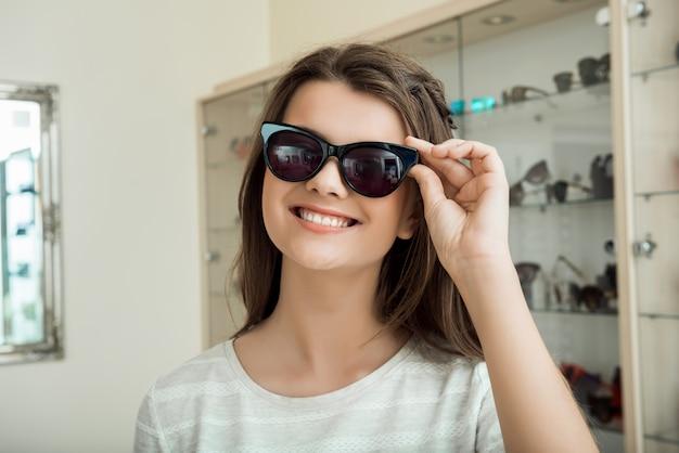 Jovem procura novos óculos de sol para acentuar seu estilo Foto gratuita