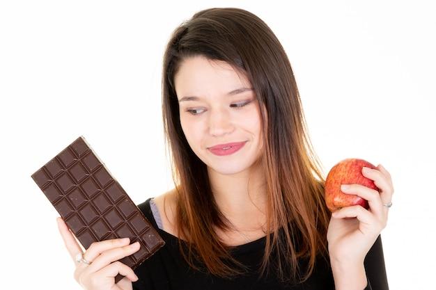 Jovem procurando maçã fresca enquanto come barra de chocolate Foto Premium
