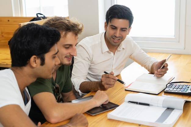 Jovem professor dizendo a dois alunos sobre orçamento corporativo Foto gratuita