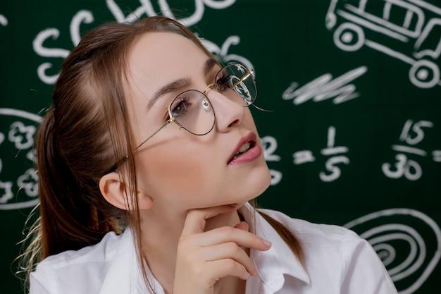 Jovem professor está sentado perto de quadro-negro em sala de aula Foto Premium
