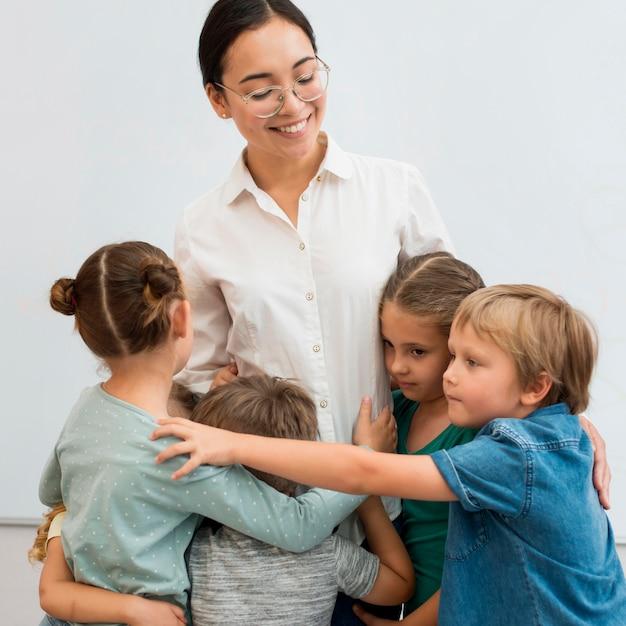 Jovem professora abraçando seus alunos Foto gratuita