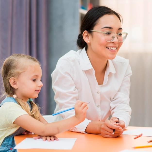 Jovem professora ajudando a menina na sala de aula Foto gratuita