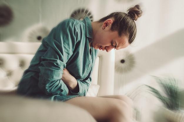 Jovem que sofre de tpm e dor menstrual no quarto em casa. tendo dor de estômago, dor abdominal por causa de dias críticos. inflamação e infecção da bexiga, cistite. Foto Premium