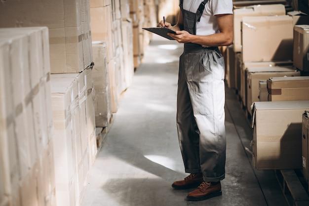 Jovem que trabalha em um armazém com caixas Foto gratuita
