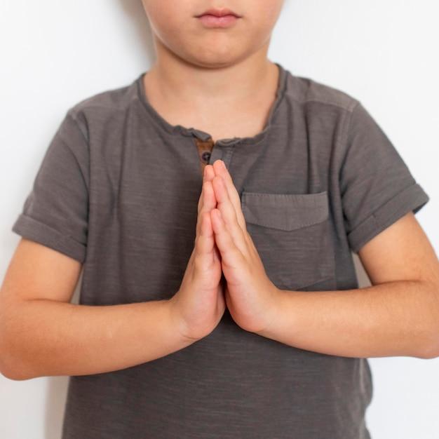 Jovem rapaz aprendendo a orar Foto gratuita