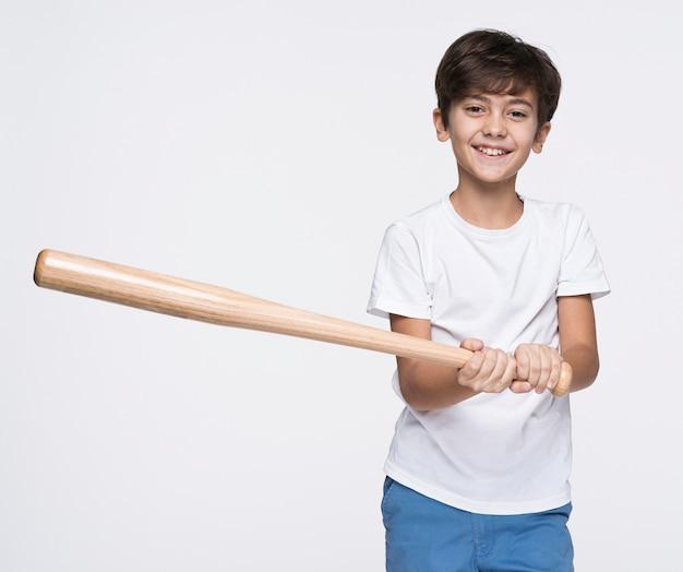 Jovem rapaz batendo com taco de beisebol Foto gratuita