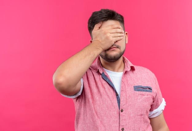 Jovem rapaz bonito vestindo uma camisa pólo rosa fazendo facepalm em pé sobre a parede rosa Foto gratuita